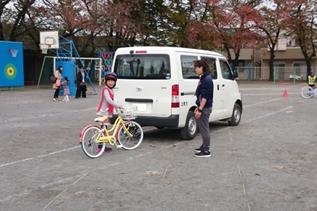 車のそばで自転車の安全確認を行う児童の写真